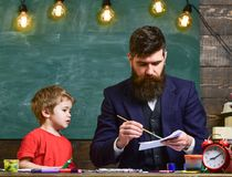 Arts lesson concept. Teacher with beard, father drawing while little son hang out near, in classroom, chalkboard on royalty free stock images