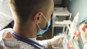 Arts met beschermende handschoenen die test-buis houden en steekproeven voor bloedtransfusie op het ziekenhuislaboratorium testen stock videobeelden
