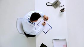 Arts met cardiogram op klembord bij kliniek stock videobeelden