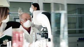 Arts met colleague do expertise door microscoop stock footage