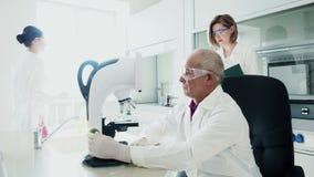 Arts met colleague do expertise door microscoop stock video