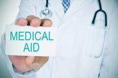 Arts met een uithangbord met de tekst medische hulp Stock Foto