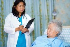 Arts met klembord voor notadiagnose van patiënten in de verzorging van het ziekenhuisafdeling stock afbeelding