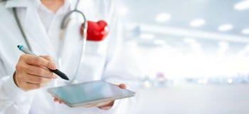 Arts met rode hartvorm en stethoscoop die digitale tablet gebruiken stock fotografie