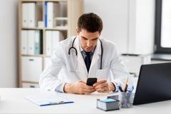 Arts met smartphone op medisch kantoor in kliniek stock foto's
