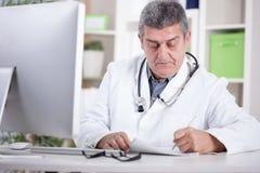 Arts met stethoscoop rond zijn hals die in bureau werken Stock Foto
