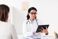 Arts met tabletpc en vrouw bij het ziekenhuis Stock Afbeeldingen