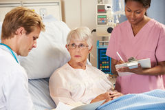 Arts met Verpleegster die aan Hogere Vrouwelijke Patiënt in Bed spreken Stock Fotografie