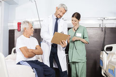 Arts And Nurse Communicating over Rapport door Hogere Patiënt royalty-vrije stock foto's