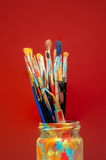 Arts painting brushes in studio jar with red background Stock Photo