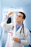 Arts resarch een medisch testglas met urine. Stock Foto