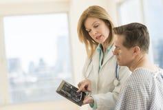 Arts Showing Digital Tablet aan Patiënt in Kliniek stock afbeeldingen