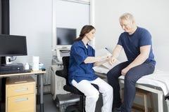 Arts Touching Male Patient & x27; s dient Kliniek in Stock Fotografie