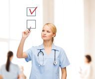 Arts of verpleegster drawning controleteken in checkbox Stock Fotografie