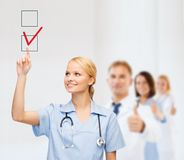 Arts of verpleegster drawning controleteken in checkbox Royalty-vrije Stock Afbeeldingen