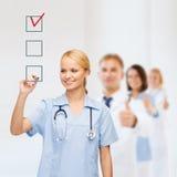 Arts of verpleegster tekeningscontroleteken in checkbox Stock Afbeeldingen