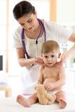 Arts wat betreft de keel van kindpatiënt in het bureau stock foto's