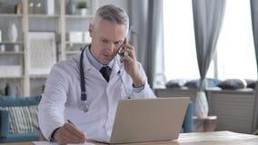 Arts Working op Laptop en het Spreken op Telefoon met Patiënt stock video