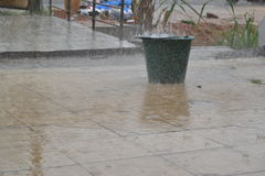 ARTSANAL PLUVIOMETRY. Bucket exposed in a pouring rain to get an approximate artisanal idea of precipitation in the form of water drops, hail that are presently Royalty Free Stock Images