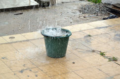 ARTSANAL PLUVIOMETRY. Bucket exposed in a pouring rain to get an approximate artisanal idea of precipitation in the form of water drops, hail that are presently Royalty Free Stock Photos