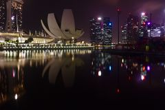 Artscience museum och kommersiella byggnader som ses in på Marina Bay under nattetid med arkivfoton