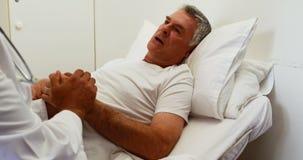 Artsen bezoekende patiënt en het houden van handen stock videobeelden