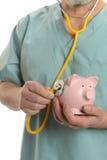 Artsen dichte omhooggaand met stethoscoop en spaarvarken Royalty-vrije Stock Foto's