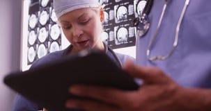 Artsen die apparaten in het bureau met behulp van Royalty-vrije Stock Foto's