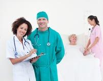 Artsen die bij een patiënt aanwezig zijn Stock Fotografie