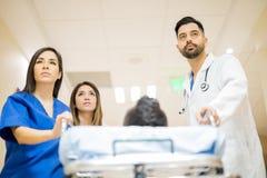 Artsen die brancard met een patiënt duwen Stock Afbeelding