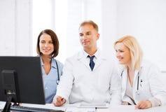 Artsen die computer op vergadering bekijken Royalty-vrije Stock Foto's