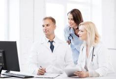 Artsen die computer op vergadering bekijken Stock Fotografie
