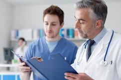 Artsen die de medische dossiers van de patiënt onderzoeken stock foto's