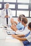 Artsen die een medearts toejuichen Stock Afbeeldingen