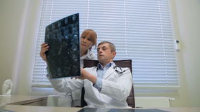 Artsen die een röntgenstraal onderzoeken stock footage