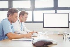 Artsen die een rapport in conferentieruimte schrijven Stock Foto