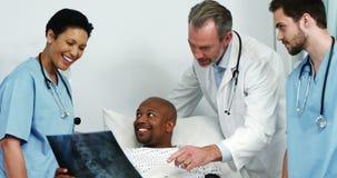 Artsen die een x-ray rapport tonen aan de patiënt stock footage