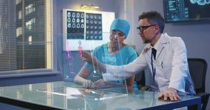 Artsen die het holografische vertoningsscherm met behulp van stock footage