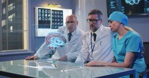 Artsen die het holografische vertoningsscherm met behulp van stock videobeelden