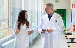 Artsen die in het ziekenhuis spreken Stock Foto's