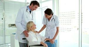 Artsen die met patiënt in rolstoel spreken stock video
