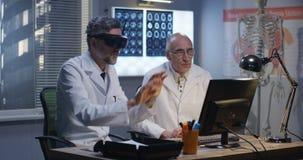 Artsen die op het scherm letten die virtuele werkelijkheidshoofdtelefoon met behulp van stock footage