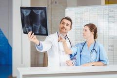 Artsen die Röntgenstraal onderzoeken door grafiek Royalty-vrije Stock Afbeelding