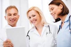 Artsen die tabletpc bekijken Stock Foto