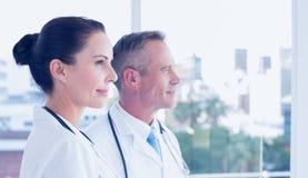Artsen die uit het venster kijken stock afbeeldingen
