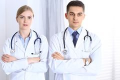 Artsen die zich rechtstreeks die met wapens bevinden in het ziekenhuis worden gekruist Artsen klaar te helpen Concept gezondheids stock foto