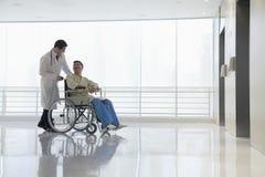 Artsen duwende en bijwonende patiënt in het ziekenhuis, Peking, China stock afbeelding