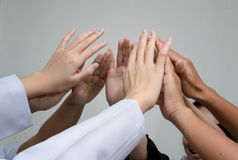 Artsen en verpleegsters in een medisch team die handen stapelen stock fotografie