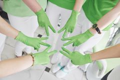 Artsen en verpleegsters in een medisch team die handen stapelen stock afbeeldingen