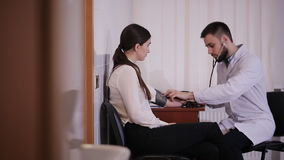 Artsen` s Bureau De mannelijke arts meet de druk van een geduldig meisje stock footage